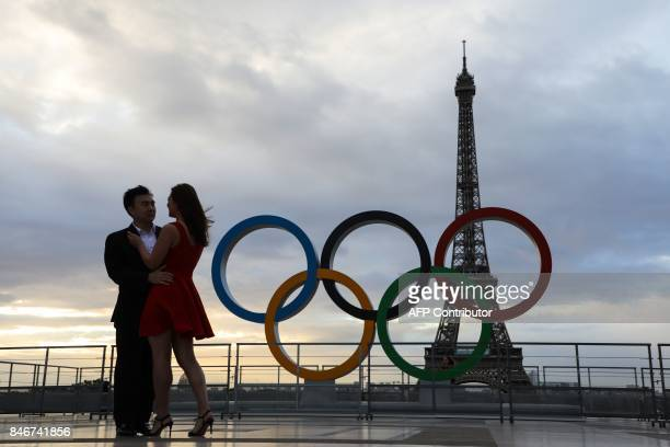 A couple is pictured at sunrise by the Olympic rings installed on the Esplanade du Trocadero near the Eiffel tower following the Paris' nomination as...