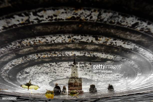 TOPSHOT A couple is reflected in a puddle as they walk past the Kremlin's Spasskaya Tower in downtown Moscow on October 12 2017 / AFP PHOTO / Kirill...