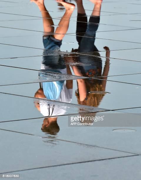 A couple is reflected in the 'Mirroir d'eau' a reflecting pool of water in Bordeaux where temperatures came close to 40 C on July 18 2017 / AFP PHOTO...