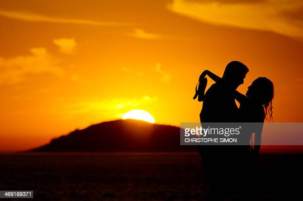 A couple is seen at the sunrise on Copacabana beach on the eve of Saint Valentin day in Rio de Janeiro on 13 februaryBrazil AFP PHOTO / CHRISTOPHE...