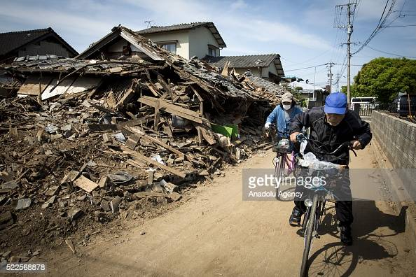 A couple is seen through the wreckage of houses on April 20 2016 in Mashiki town Kumamoto Japan At least 41 people were killed and over 180000 people...
