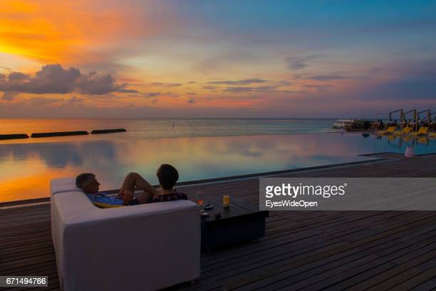 A couple is watching the Colourful Sunset at Coco Bodu Hiti NorthMaleAtoll on February 26 2017 in Male Maldives