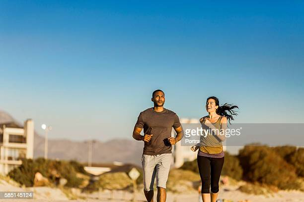 Couple jogging at beach against clear blue sky