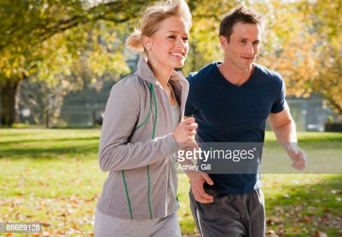 Couple jogging in park in autumn : Foto de stock