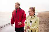 Couple jogging on the beach in cold weather