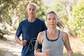 Senior man and woman jogging in park while listening to music. Mature couple running at park together. Retired man and mid woman exercising outdoor.