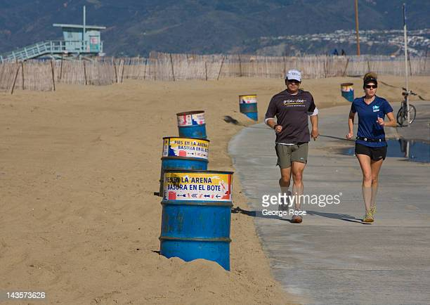 A couple jogs along the beach path near the pier on April 14 2012 in Santa Monica California Millions of tourists flock to the Los Angeles area to...