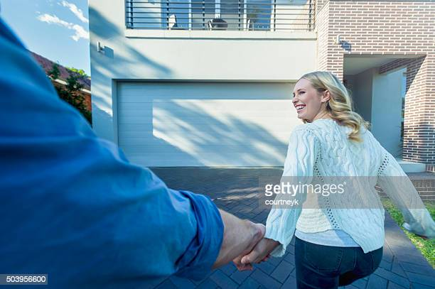 Couple joyfully running into their new home.