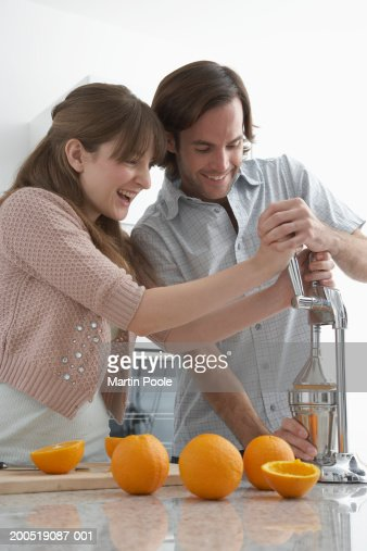 Couple juicing oranges in kitchen, smiling : Stock Photo