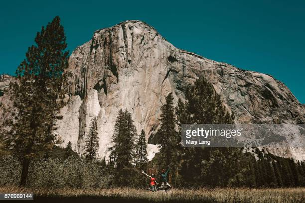 Couple jumping by El Capitan in the meadow Yosemite National Park California USA