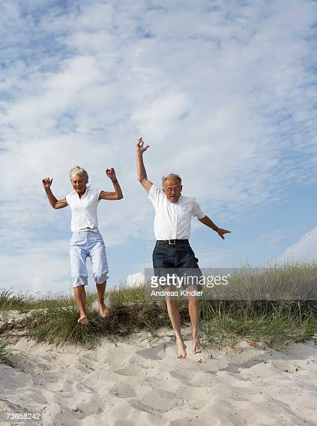 Couple jumping down in to the sand.