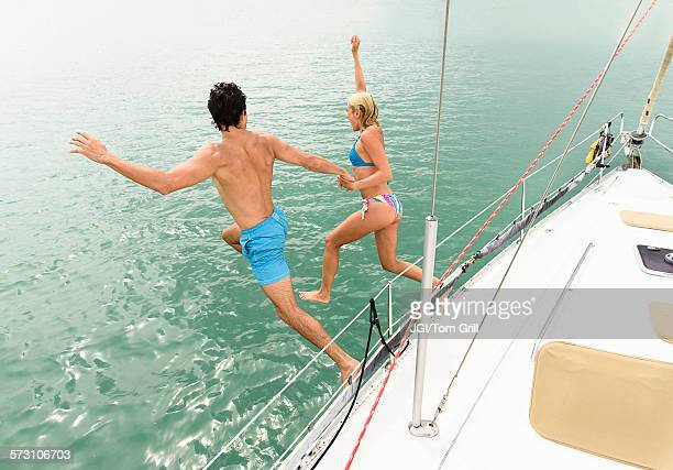Couple jumping from sailboat deck into ocean