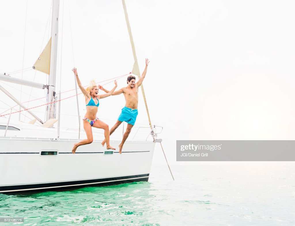Couple jumping from sailboat
