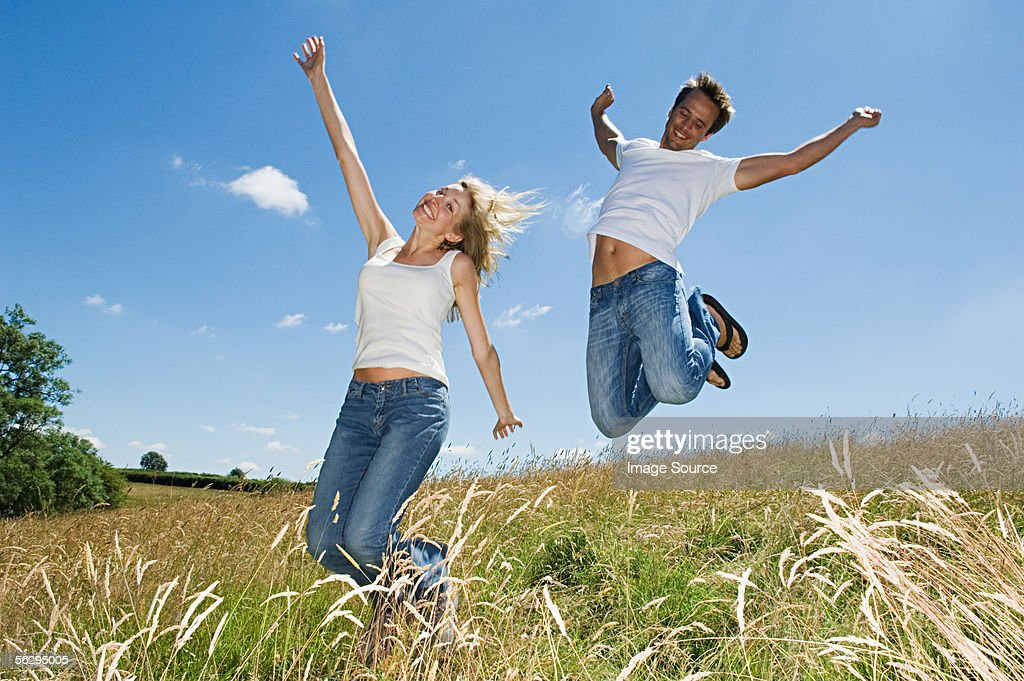 Couple jumping in a field : Stock Photo