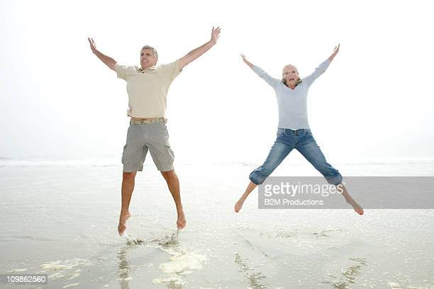 Couple jumping in the air on beach