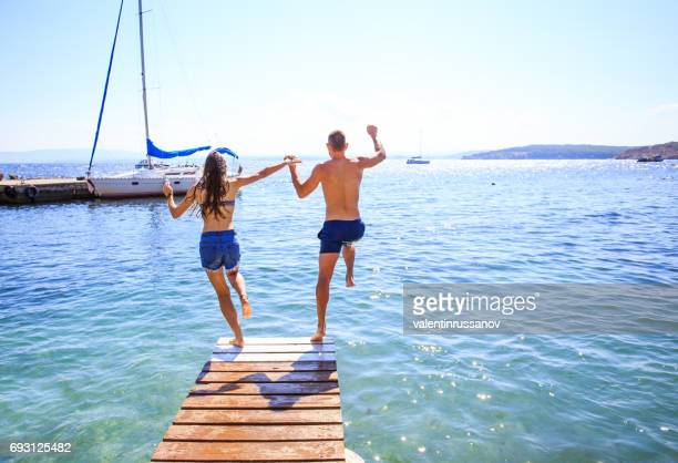 Couple jumping into water