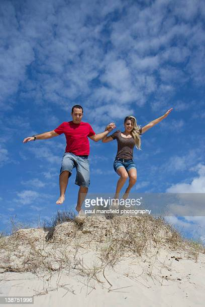 Couple jumping off sand dune
