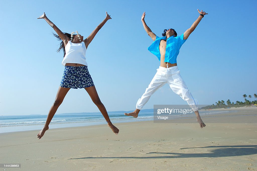 Couple jumping on a beachside : Stock Photo
