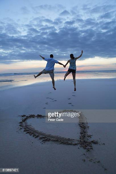 Couple jumping on beach, heart drawn in sand