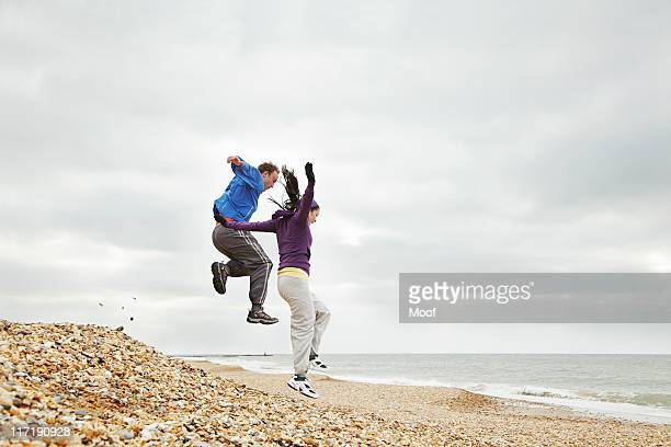 Couple jumping on beach on cloudy day