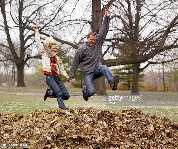 Couple jumping on heap of dry leaf, laughing