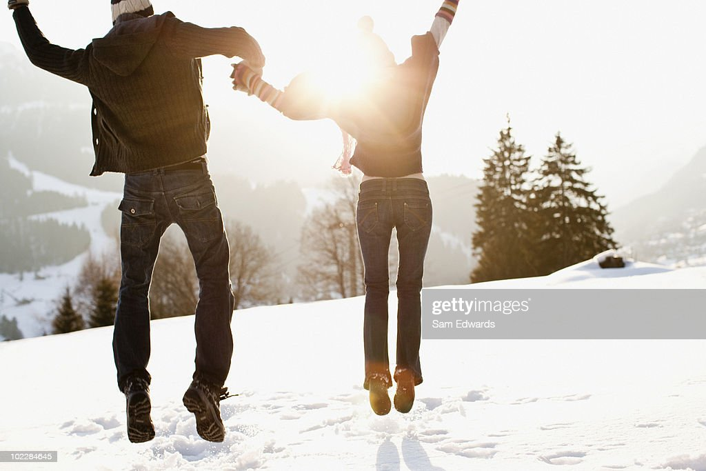 Couple jumping outdoors in snow : Stock Photo