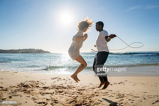 Couple jumping rope at the beach