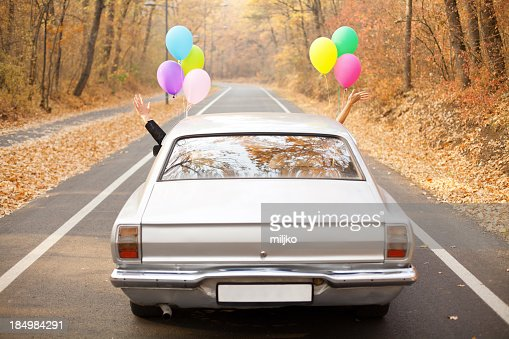 A couple just married with balloons tied to their car