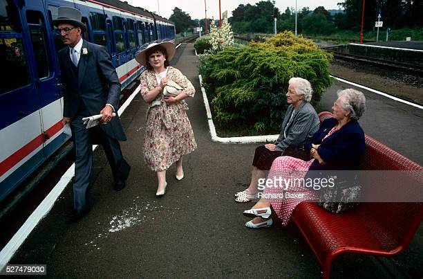A couple just off the train from Waterloo are enroute to Ascot racecourse on Ladies Day at Royal Ascot racing week Not looking particularly happy to...