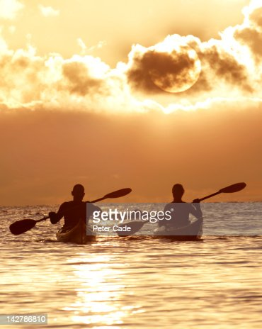 couple kayaking at sunset : Stock Photo