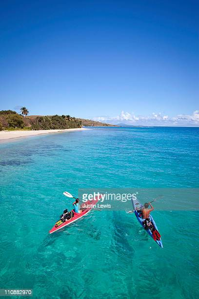 Couple kayaking in tropical setting.