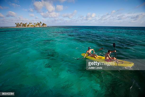 couple kayaking with small tropical Island