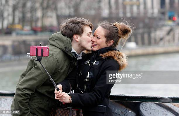 A couple kiss and take a selfie on the Pont Des Arts during Valentine's Day on February 14 2014 in Paris France Officials from Paris City Hall have...