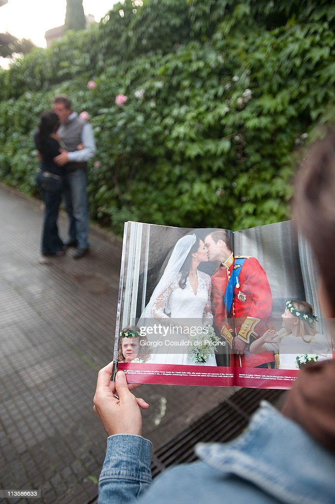 A couple kiss as a girl reads an Italian magazine showing photographs of Prince William, Duke of Cambridge and Catherine, Duchess of Cambridge following their wedding, on May 3, 2011 in Rome, Italy. The marriage of the second in line to the British throne was led by the Archbishop of Canterbury and was attended by 1900 guests, including foreign Royal family members and heads of state. Thousands of well-wishers from around the world flocked to London to witness the spectacle and pageantry of the Royal Wedding.