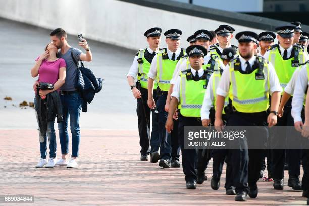 A couple kiss as police make their way to the stadium in London on May 27 2017 ahead of the English FA Cup final football match between Arsenal and...