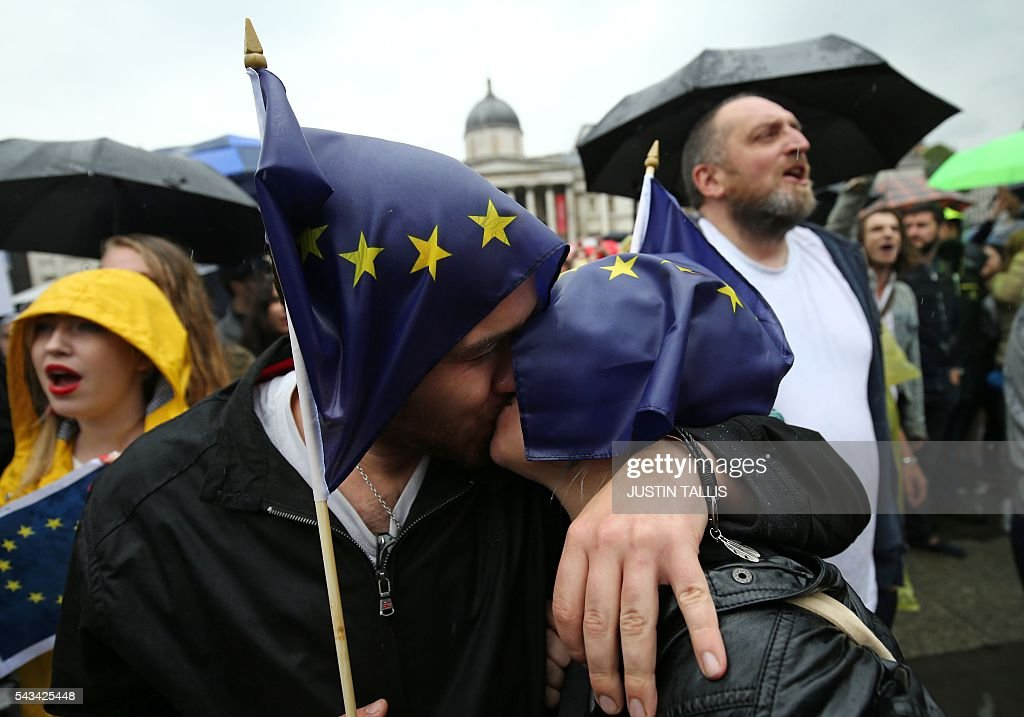 A couple kiss as they hold European flags at an anti-Brexit protest in Trafalgar Square in central London on June 28, 2016. EU leaders attempted to rescue the European project and Prime Minister David Cameron sought to calm fears over Britain's vote to leave the bloc as ratings agencies downgraded the country. Britain has been pitched into uncertainty by the June 23 referendum result, with Cameron announcing his resignation, the economy facing a string of shocks and Scotland making a fresh threat to break away. / AFP / JUSTIN
