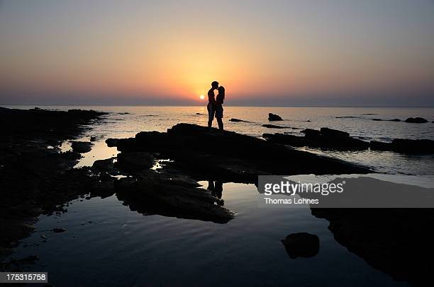 A couple kiss as they pose on beach against the backdrop of a sunset on July 28 2013 in 28 Savutrija Croatia