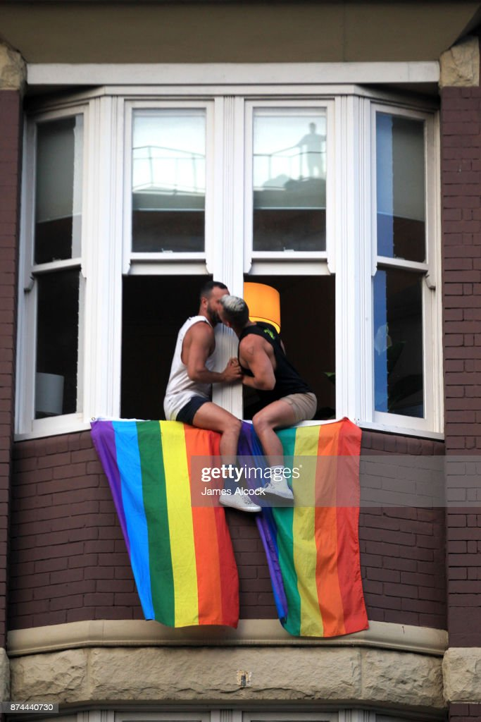 A couple kiss as they sit at their window as crowds supporting the Same Sex marriage Survey march down Oxford St and into the city whilst a same sex couple embrace above in a window on November 15, 2017 in Sydney, Australia. Australians have voted for marriage laws to be changed to allow same-sex marriage, with the Yes vote claiming 61.6% to to 38.4% for No vote. Despite the Yes victory, the outcome of Australian Marriage Law Postal Survey is not binding, and the process to change current laws will move to the Australian Parliament in Canberra.