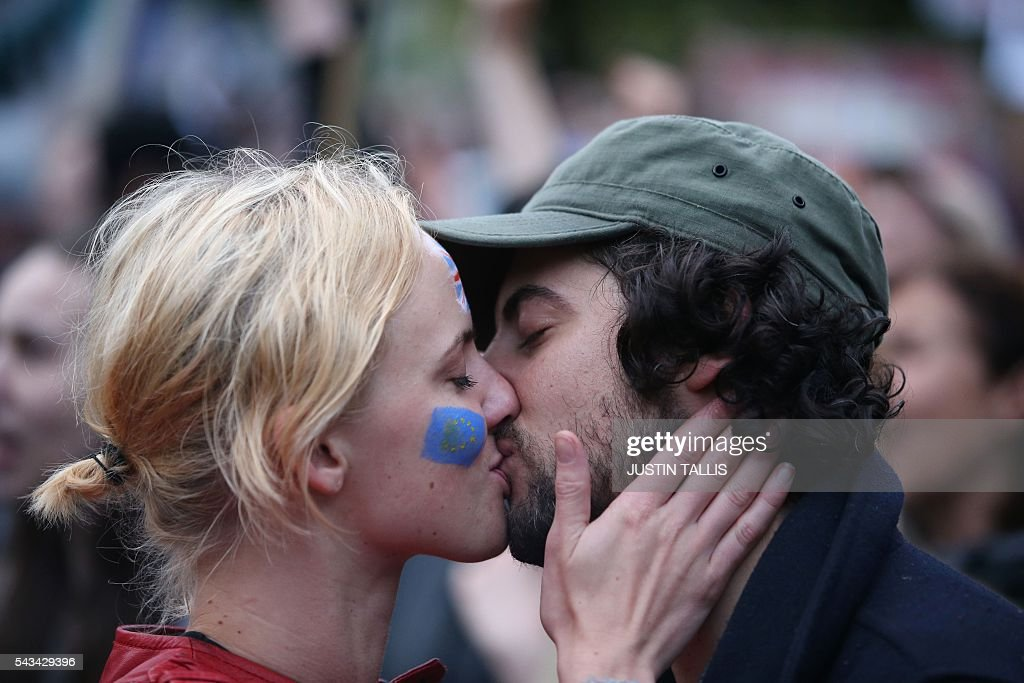 A couple kiss at an anti-Brexit protest in Trafalgar Square in central London on June 28, 2016. EU leaders attempted to rescue the European project and Prime Minister David Cameron sought to calm fears over Britain's vote to leave the bloc as ratings agencies downgraded the country. Britain has been pitched into uncertainty by the June 23 referendum result, with Cameron announcing his resignation, the economy facing a string of shocks and Scotland making a fresh threat to break away. / AFP / JUSTIN