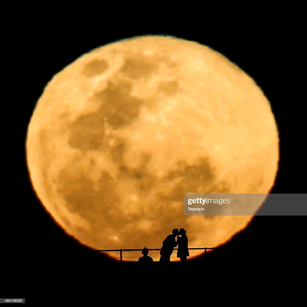 A couple kiss during a full supermoon, as it rises over North Bondi headland on September 9, 2014 in Sydney, Australia. A supermoon or harvest moon involves a full moon coinciding with it's closest approach to the Earth on it's elliptical orbit.