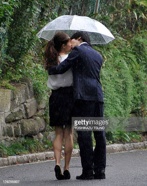 A couple kiss during heavy rain along a street in Yokohama suburban Tokyo on October 15 2011 Heavy rains hit the Pacific coastal areas in Japan...