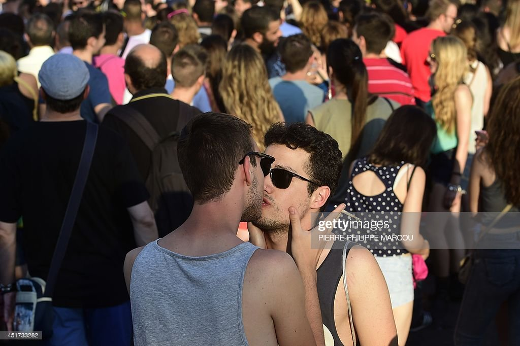 A couple kiss during the Gay Pride Parade in Madrid on July 5, 2014. Crowds of revellers in elaborate costumes filled the streets of central Madrid today in what organisers billed the biggest gay pride parade in Europe. Organisers expected more than a million people at the evening parade, the main event in five days of festivities by defenders of lesbian, gay, bisexual and transgender (LGBT) rights.