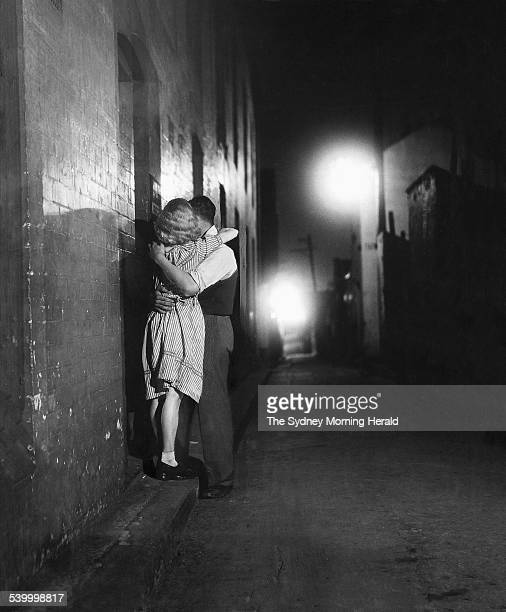 A couple kiss in a dimly lit Surry Hills alley With mum dad grandma and the siblings a hindrance to young lovers' privacy at home they stole it back...
