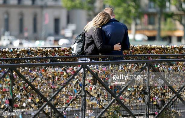 A couple kiss in front of Love padlocks on the 'Pont Neuf' on April 29 2017 in Paris France The Paris City Hall will organize on May 13th an auction...