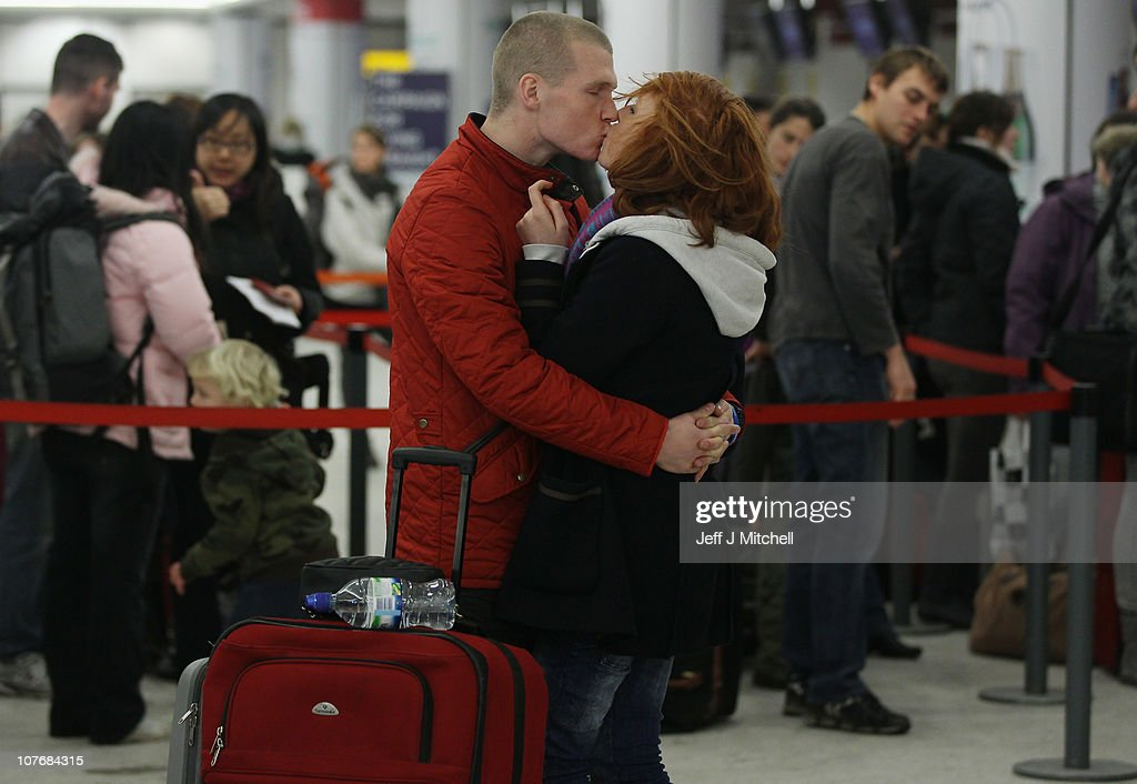 A couple kiss in the airport as they and other passengers face delays to their flights following disruption due to snow at Edinburgh Airport on December 19, 2010 in Edinburgh, Scotland. The United Kingdom is continuing to suffer heavy snowfall causing delays at many airports and closure of major roads.