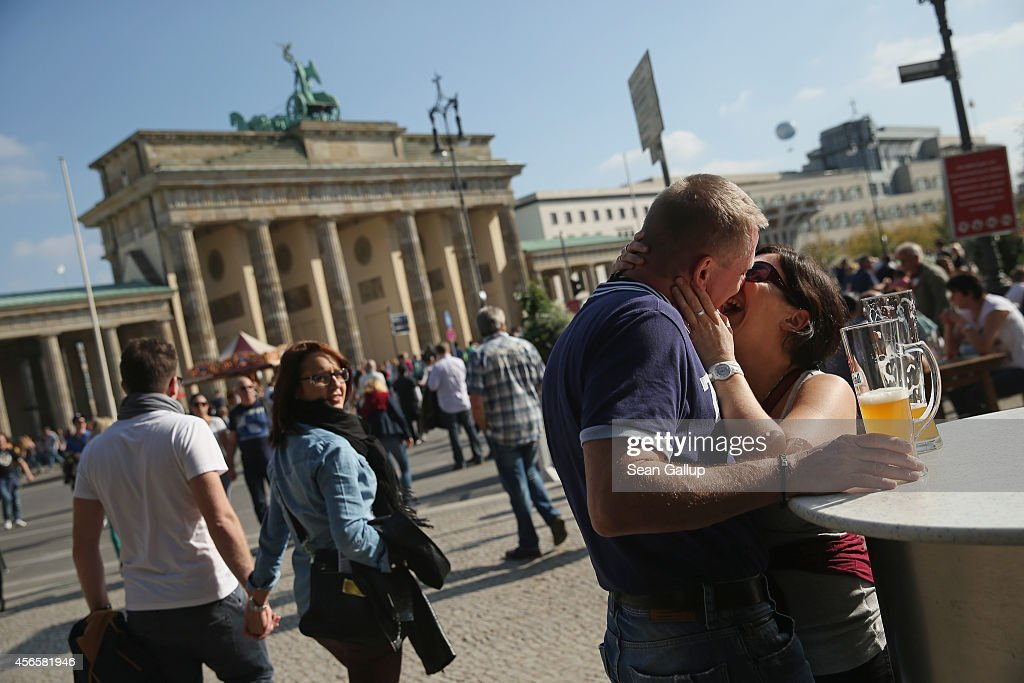 A couple kiss near the Brandenburg Gate on German Unity Day (Tag der Deutschen Einheit) on October 3, 2014 in Berlin, Germany. Germany is celebrating the 24th anniversary of the day when former West Germany and East Germany reunited into modern Germany in 1990 following the end of the Cold War. This year Germany will also celebrate the 25th anniversary of the fall of the Berlin Wall that heralded the collapse of communist authority in East Germany.