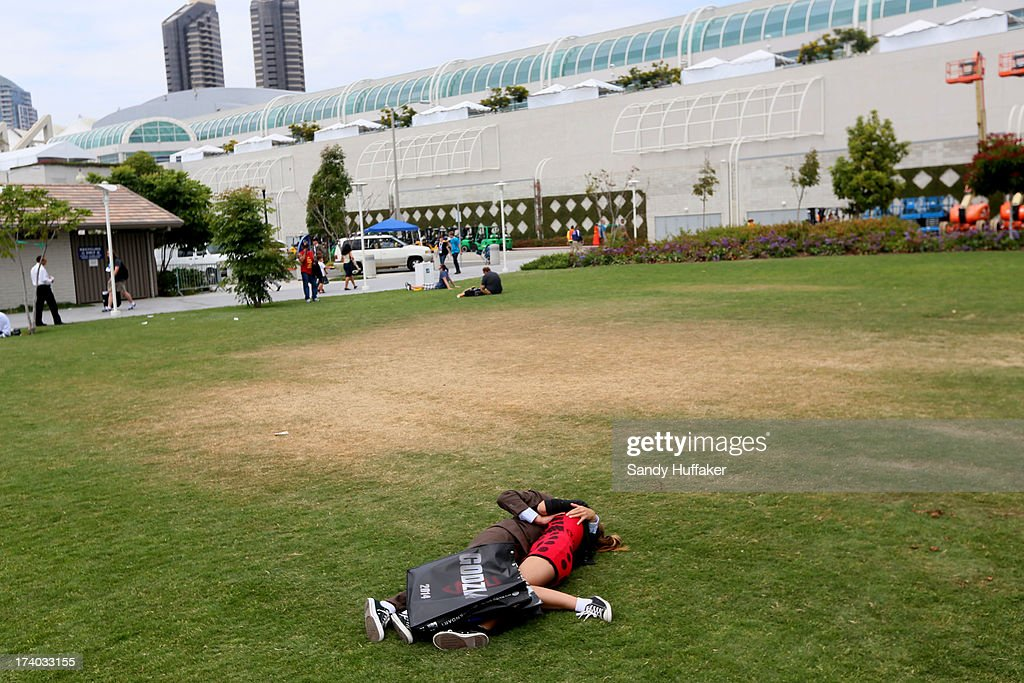 A couple kiss on the lawn outside the Convention Center during Comic Con on July 19, 2013 in San Diego, California. The Comic Con International Convention is the world's largest comic and entertainment event and hosts celebrity movie panels, a trade floor with comic book, science fiction and action film-related booths, as well as artist workshops and movie premieres.
