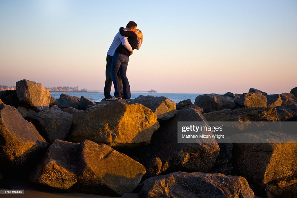 A couple kiss passionately at sunset : Stock Photo