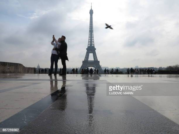 A couple kiss takes a selfie on the Human Rights Esplanade place du Trocadero in front of the Eiffel tower in Paris on March 24 2017 / AFP PHOTO /...