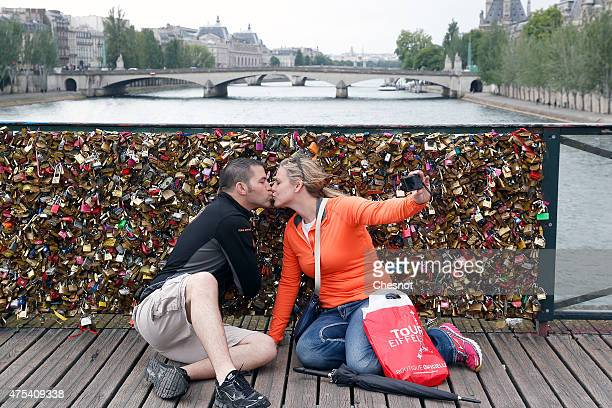 A couple kisses and takes a selfie in front of the love Padlocks on the 'Pont des arts' on May 31 2015 in Paris France The Paris City hall announced...